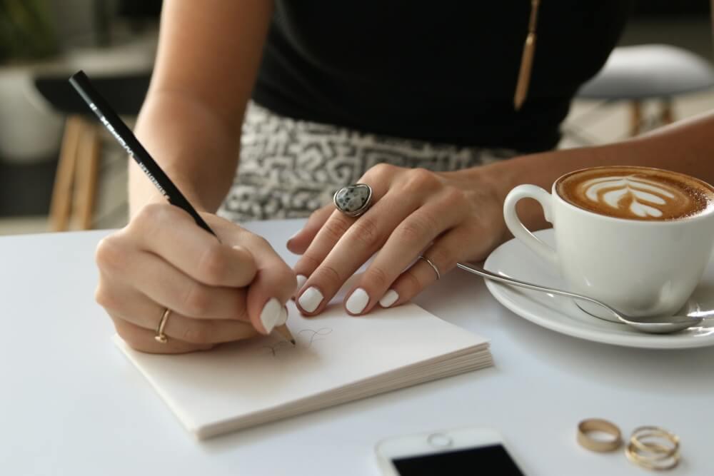 カフェでメモをとる女性。フリー素材